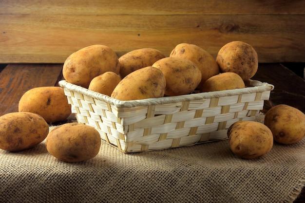 As batatas frescas e cruas colhidas da plantação e colocadas em uma caixa rústica na mesa de madeira.