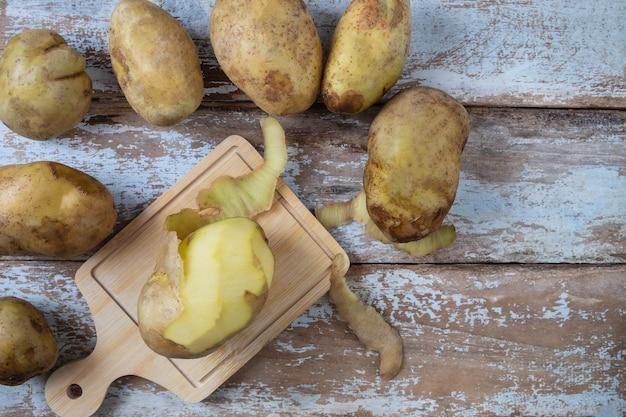 As batatas são descascadas no fundo de madeira.