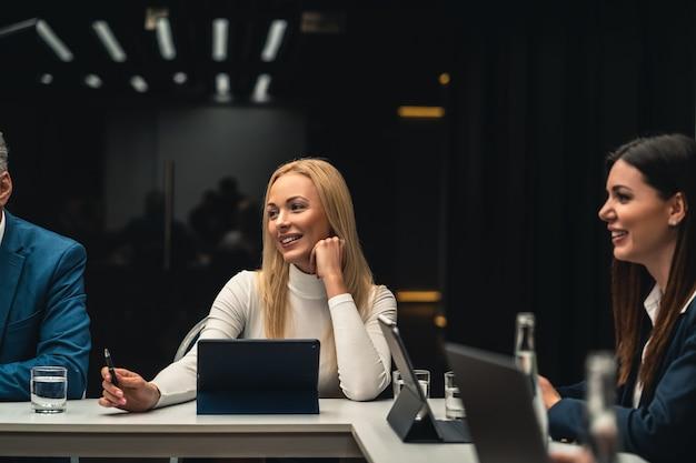 As belas empresárias sentadas à mesa na conferência de negócios