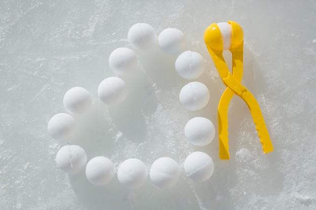 As bolas de neve são dispostas no gelo em forma de coração ao lado da ferramenta de escultura de bola de neve