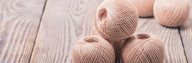 As bolas do fio rosqueiam para fazer malha em um fundo de madeira.
