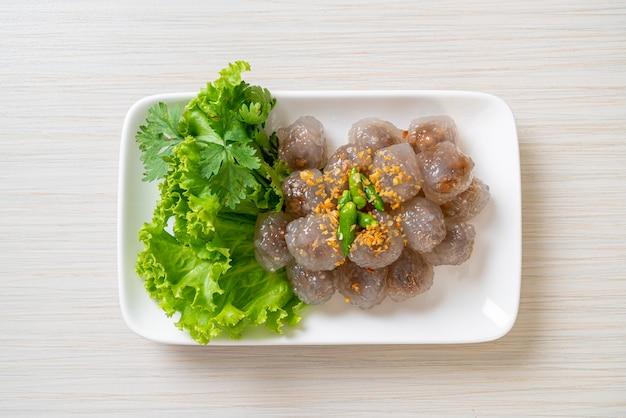 As bolas transparentes são chamadas de saku sai moo ou bola de bolinhos de tapioca cozida no vapor com recheio de carne de porco