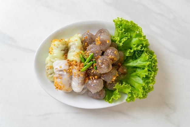 As bolas transparentes são chamadas saku sai moo ou bolinhos de tapioca no vapor com recheio de carne de porco e (kow griep pag mor) parcelas de arroz no vapor de carne de porco ou bolinhos de casca de arroz no vapor