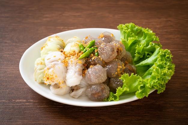 As bolas transparentes são chamadas saku sai moo ou bolinhos de tapioca no vapor com recheio de carne de porco e (kow griep pag mor) parcelas de arroz no vapor de carne de porco ou bolinhos de pele de arroz cozido no vapor