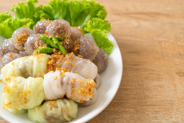 As bolas transparentes são chamadas saku sai moo ou bolinhos de tapioca no vapor com recheio de carne de porco e (kow griep pag mor) parcelas de arroz no vapor de carne de porco ou bolinhos de pele de arroz no vapor