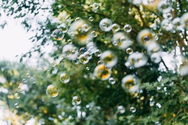 As bolhas de sabão do arco-íris do soprador de bolhas com bokeh bonito