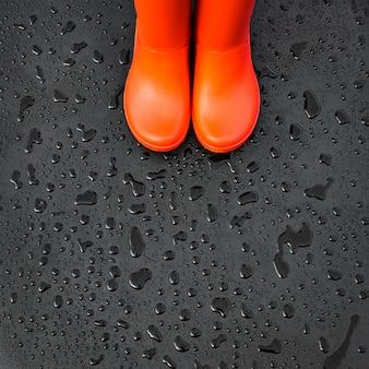 As bordas das botas de chuva laranja estão em uma superfície úmida e molhada coberta com gotas de chuva.