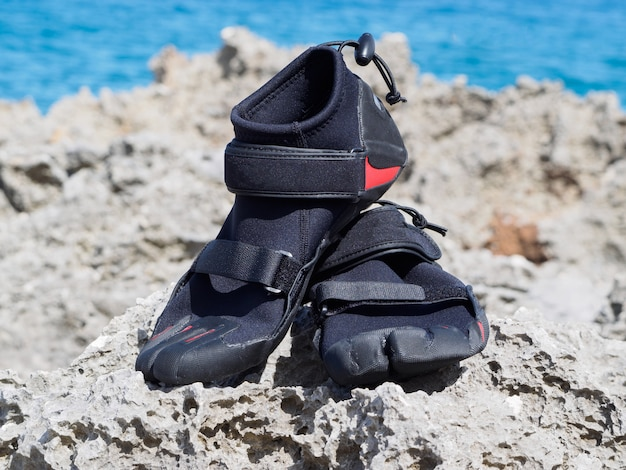 As botas de recife estão sobre corais e recifes. perto do oceano. dia ensolarado.