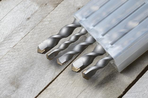 As brocas com brocas de martelo com ponta de carboneto encontram-se em uma caixa de plástico sobre um fundo de prancha de madeira. fechar-se.