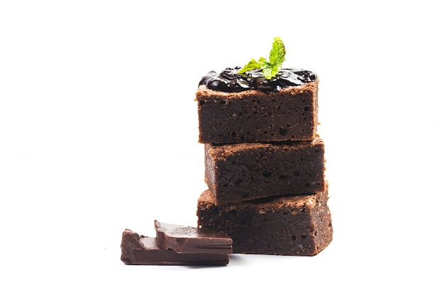 As brownies caseiros cortadas elevam-se no fundo branco do isolado. doce e úmido de sobremesa de chocolate.
