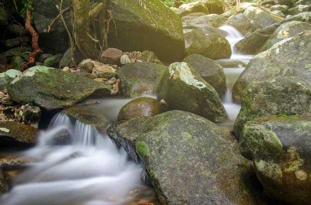 As cachoeiras fluem através das rochas em parques nacionais com fundos borrados.