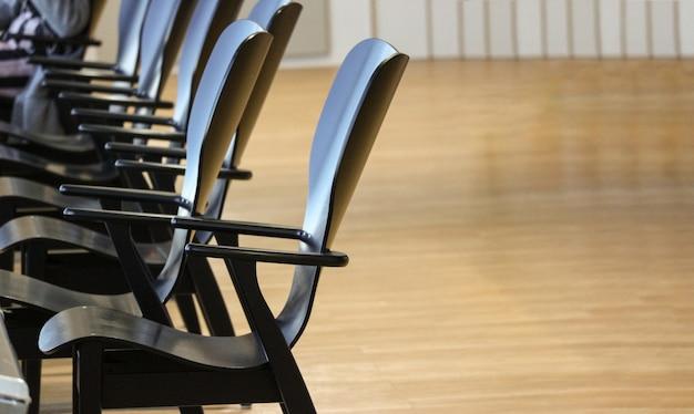 As cadeiras de madeira do preto do café de empoty enfileiram com espaço da cópia.
