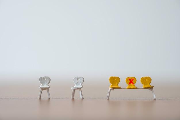 As cadeiras em miniatura amarelas que têm a marca da cruz vermelha para proibir se sentam para manter distância pública e impedir que o surto de vírus corona covid-19 espalhe infecção pandêmica. conceito de distanciamento social.