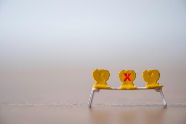 As cadeiras em miniatura amarelas que têm a marca da cruz vermelha para proibir se sentam para manter distância pública e impedir que o surto de vírus corona covid-19 espalhe infecção pandêmica.