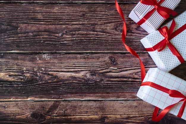 As caixas de presente do natal e do ano novo em woodden o fundo.