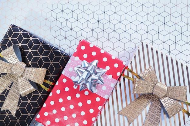 As caixas de presente são de ouro preto com um laço dourado, de ervilhas vermelhas a brancas com um laço prateado e brancas com listras douradas e um laço dourado inclinado em papel branco