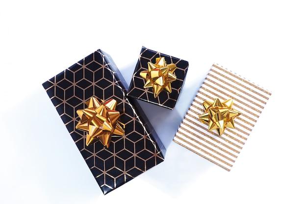 As caixas de presente são de ouro preto com um padrão geométrico e um laço dourado e preto com uma tampa branca e dourada brilhante e um laço dourado.