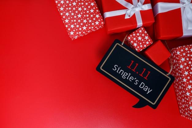 As caixas de presente vermelhas sobre fundo vermelho com espaço de cópia para a venda do dia do único texto 11,11.