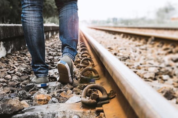 As calças de brim do desgaste de mulher e as sapatas da sapatilha andam na estrada de ferro do trem,