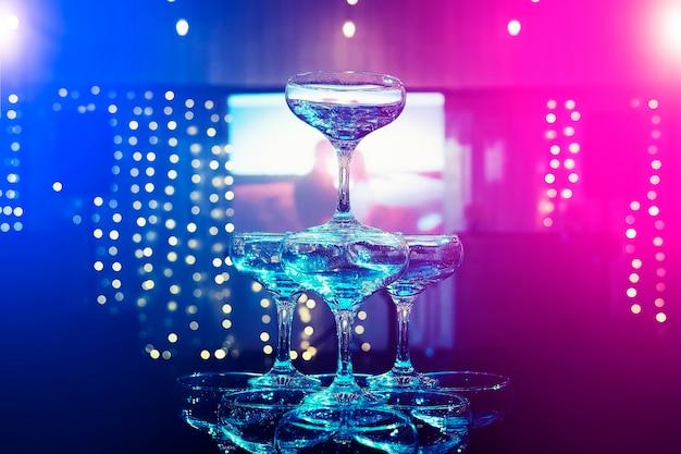 As camadas superiores da torre de champanhe no fundo desfocado de uma tela de projetor em um salão de banquete de casamento. lindo conjunto de óculos cupê no fundo de projeção do casal apaixonado. casamento de luxo.