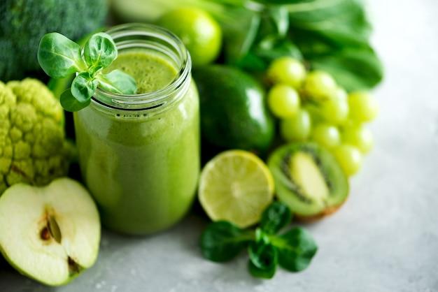 As canecas de vidro do frasco com o batido verde da saúde, couve saem, cal, maçã, quivi, uvas, banana, abacate, alface.