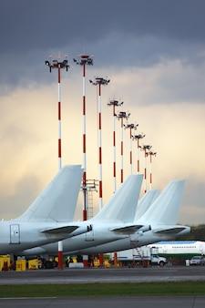 As caudas dos aviões estacionaram no avental do aeroporto contra um céu nebuloso.