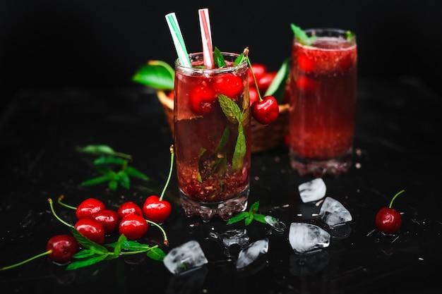 As cerejas frescas colocadas em uma cesta e as cerejas pretas com água espirram.