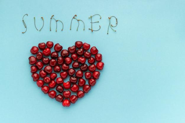 As cerejas vermelhas da baga dão forma ao coração e ao texto verão no fundo azul copie o espaço