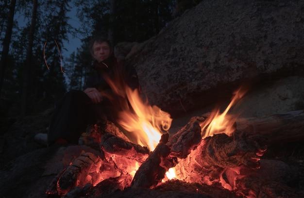 As chamas da fogueira fecham-se. o homem ao fundo