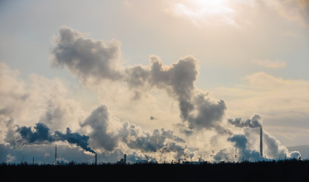 As chaminés das fábricas poluem a atmosfera com uma fumaça densa.