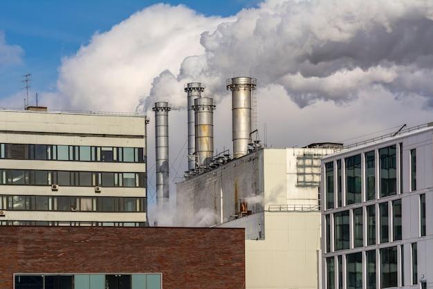 As chaminés de fumar de fabricação de fábricas e edifícios de escritórios