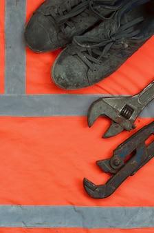 As chaves ajustáveis e as botas velhas encontram-se em uma camisa alaranjada do trabalhador do sinal