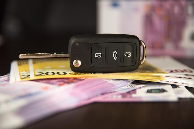 As chaves do carro para o empréstimo de simulação do euro para a compra do carro cédulas. aluguel de carro ou compra, dinheiro do euro com as chaves.