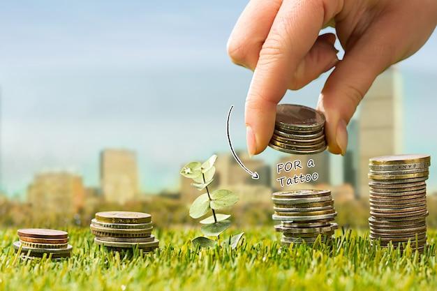 As colunas de moedas na grama verde e mão feminina. conceito financeiro de poupança e investimento