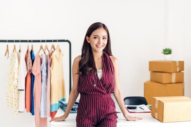As compras em linha do negócio do freelancer da jovem mulher olham a câmera com a caixa de papelão na tabela em casa. conceito de envio e entrega on-line de negócios