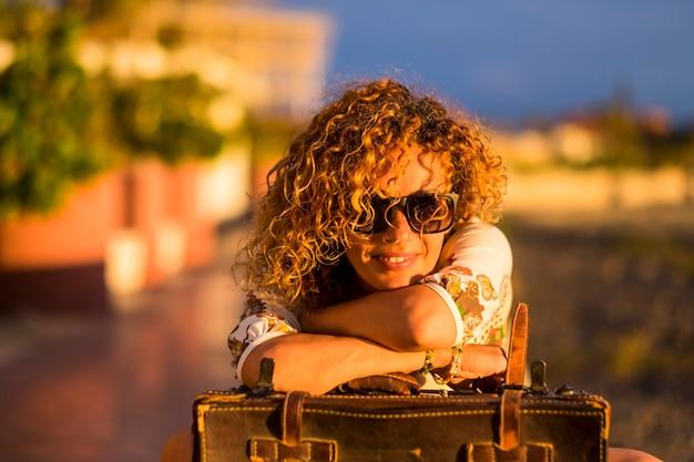 As cores do retrato da hora do pôr do sol de uma bela jovem adulta relaxam nas atividades de lazer sozinha - sorria e viaje com uma bagagem vintage à moda antiga