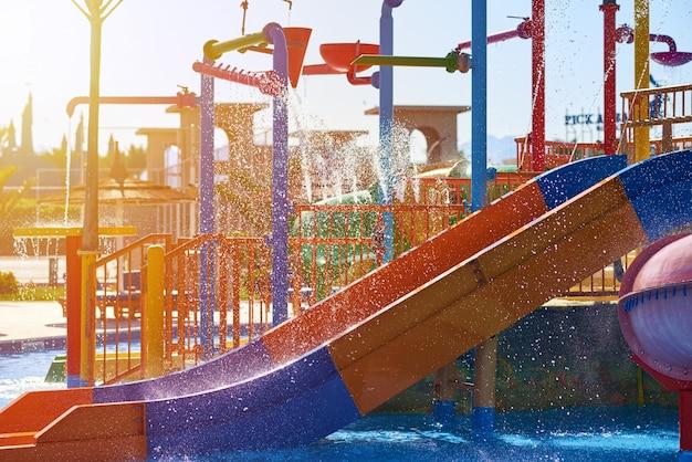 As corrediças coloridas no parque aquático fecham-se acima. controles deslizantes aquapark com piscina