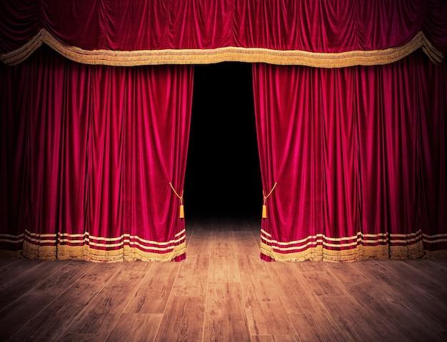 As cortinas vermelhas do palco se abrem para o espetáculo de teatro