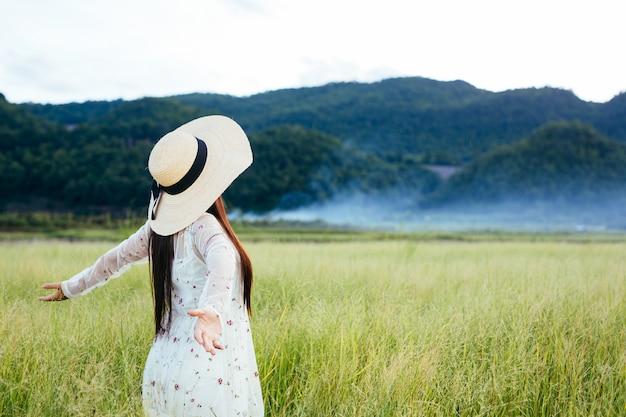 As costas de uma mulher bonita que está feliz no prado com uma grande montanha como um.