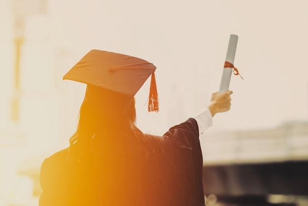 As costas dos formandos usam boné na universidade.