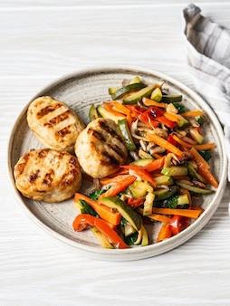 As costeletas de turquia grelham, os bois dos vegetais fritam em um prato na tabela da placa de madeira.