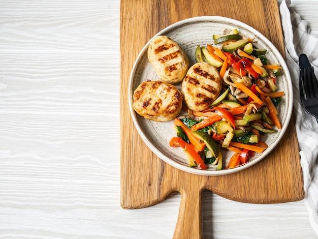 As costeletas de turquia grelham, os legumes dirigem fritam em um prato na mesa na placa de madeira.