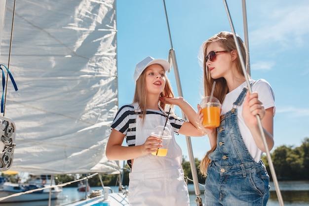 As crianças a bordo do iate do mar bebendo suco de laranja. as meninas adolescentes ou crianças contra o céu azul ao ar livre. roupas coloridas. conceitos de moda infantil, verão ensolarado, rio e feriados.