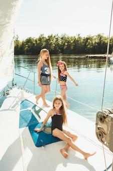 As crianças a bordo do iate do mar bebendo suco de laranja. as meninas adolescentes ou crianças contra o céu azul ao ar livre. roupas coloridas. conceitos de moda infantil, verão ensolarado, rio e feriados. Foto gratuita