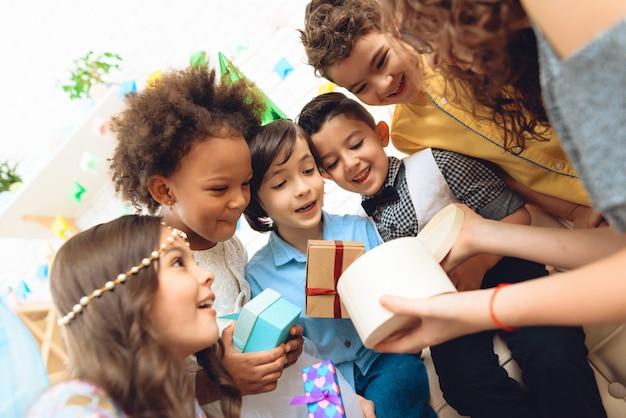 As crianças alegres olham na caixa de presente mantida pela menina do aniversário.