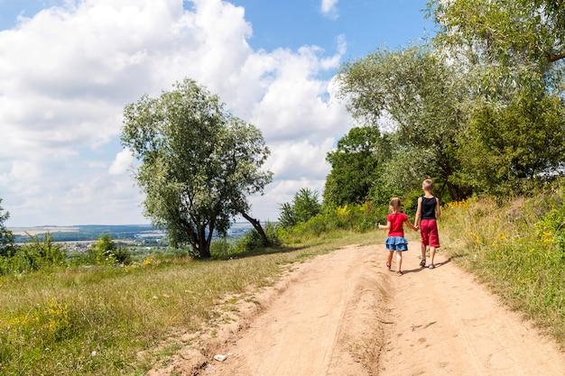 As crianças andam em uma estrada de terra