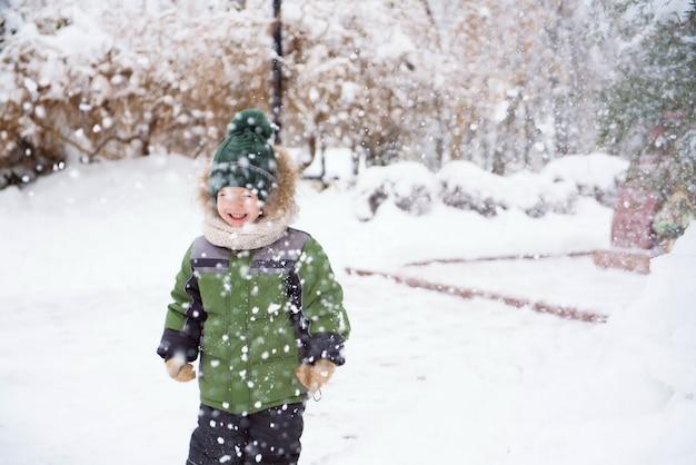 As crianças andam no parque com a primeira neve
