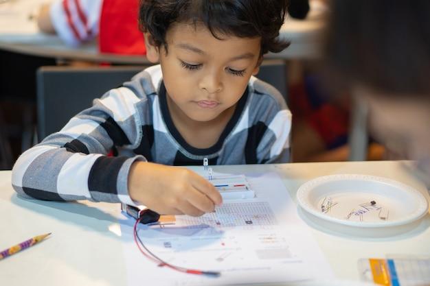 As crianças aprendem a conectar circuitos elétricos na sala de aula.