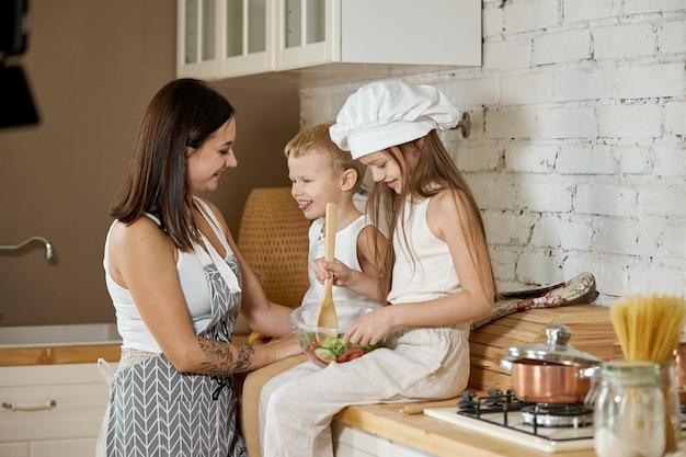 As crianças aprendem a preparar uma salada na cozinha. dia de folga em família, almoço com as próprias mãos. mãe e jovens cozinheiras