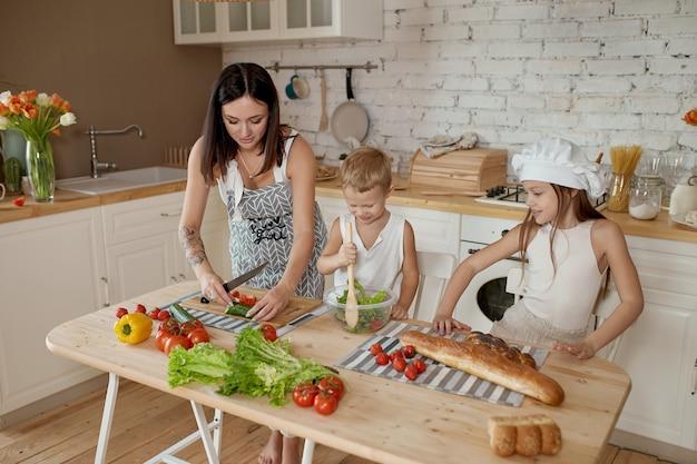 As crianças aprendem a preparar uma salada na cozinha
